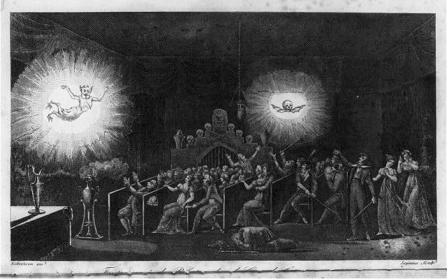 A crowd is frightened by images of the devil and a death's head floating above them in the dark.