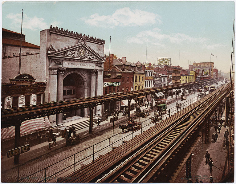 Image of the Bowery with people walking on the street, horse-drawn carts, and trolleys below an elevated train track in front of the Bowery Savings Bank.