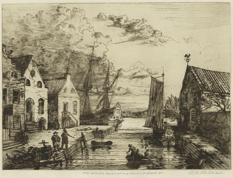 The image shows a canal with buildings on either side. There are small rowboats in the water. Two men stand at a dock.