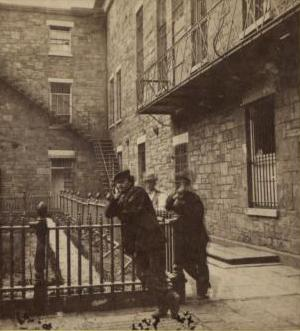 Three men stand around an iron fence in the courtyard of the Tombs. It is a stone building with grates on the windows.