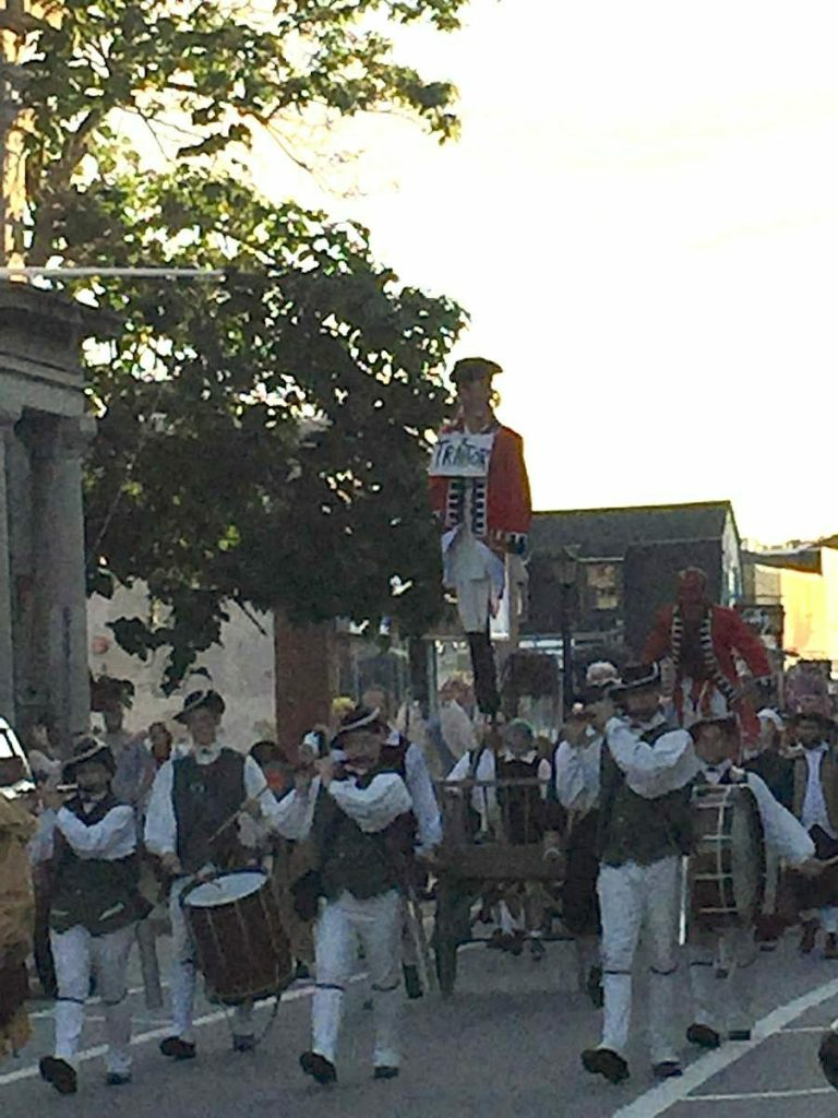 A parade of re-enactors of the American Revolution carrying a Benedict Arnold effigy to where it will burn.
