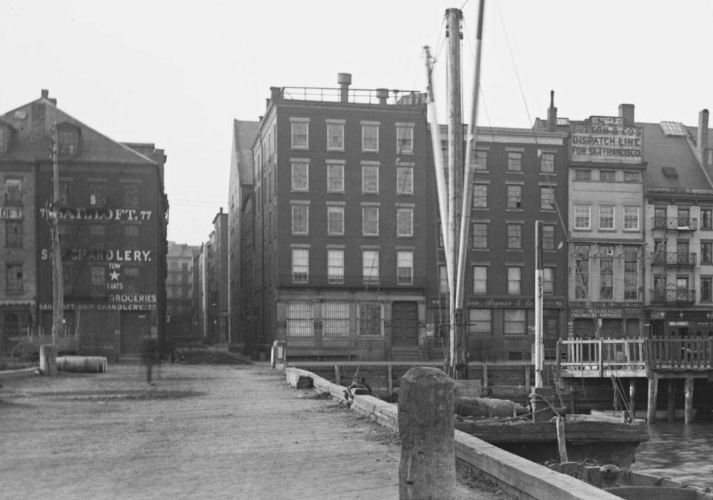 Black and white photograph with warehouses in the background and a slip in the foreground. South Street from Maiden Lane to Burling Slip, New York City, February 23, 1891