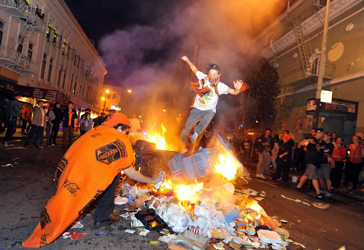 Bonfire with man jumping over it in the middle of a city street.