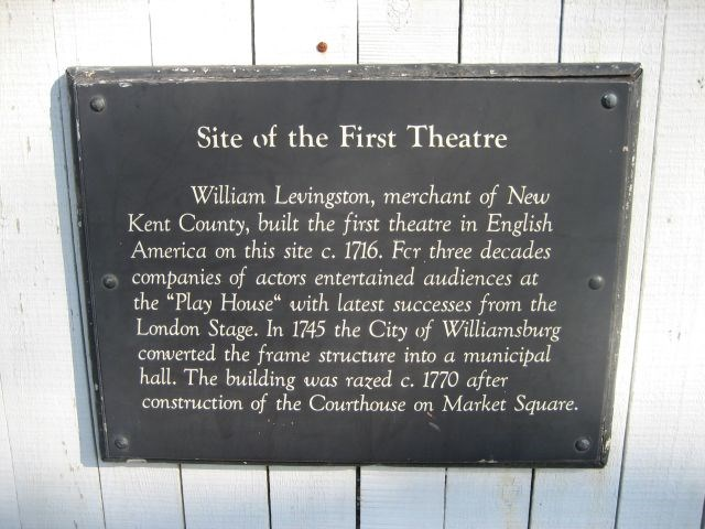 """(A plaque) Site of the First Theatre: William Levingston, merchant of Kent County, built the first theatre in English America on this site c. 1716. For three decades companies of actors entertained audiences at the """"Play House"""" with latest successes from the London Stage. In 1745 the City of Williamsburg converted the frame structure into a municipal hall. The building was razed c. 1745 after the construction of the Courthouse on Market Square."""