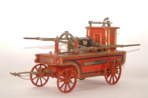 Small red fire engine that would be drawn by horse, water hand-pumped