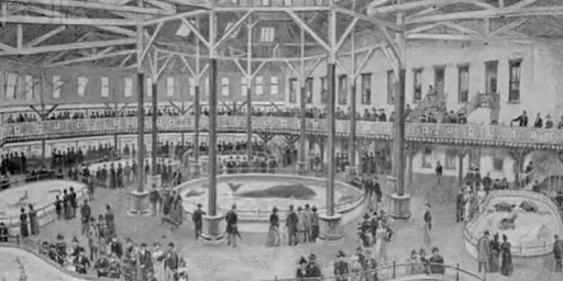 Interior view of the Castle Garden Aquarium. Two floors are seen. On the first floor are large tanks with sea animals within. Many people are present.