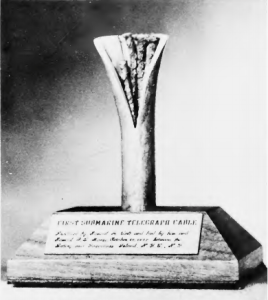 A segment of underwater telegraph cable splayed open to see the strands inside, mounted on a trophy block. A plaque says: First Submarine Telegraph Cable