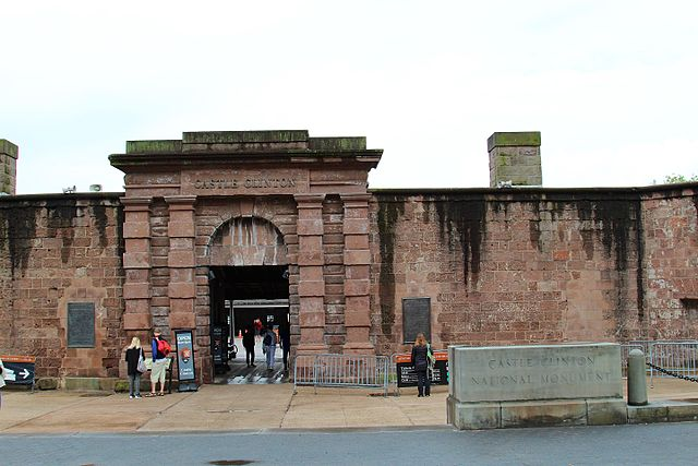 Front of Castle Clinton National Monument. People gather in front of the walls reading signs.
