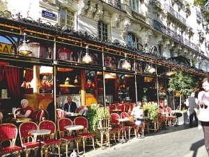 French restaurant with tables set out on the sidewalk.