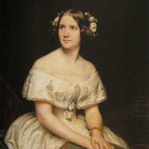 Jenny Lind with her hair decorated with flowers, she's wearing an off-the-shoulder gown.