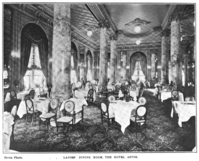 A large dining room with thick marble columns between the decorative ceiling and carpeting. Tables of four seats are spread throughout.